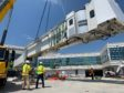 Workers install a jet bridge at the new concourse under construction at Reagan National Airport in Arlington. Photo courtesy MWAA/Project Journey